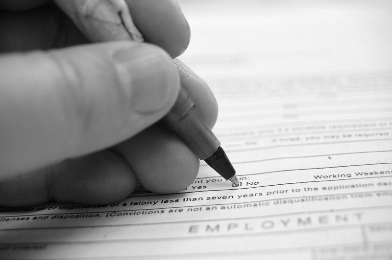 Photo of hand filling out application form with pen