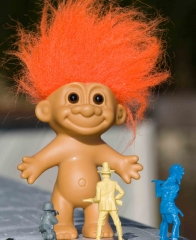 Troll doll surrounded by toy soldiers