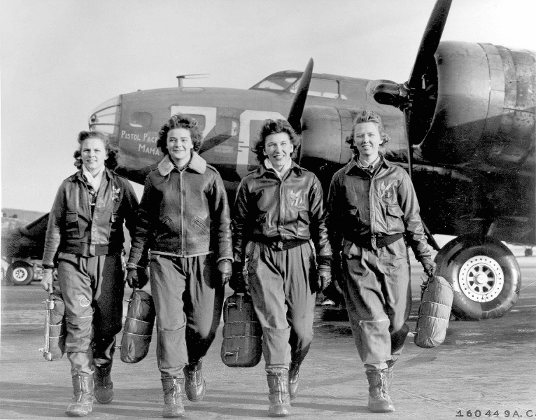 Four women walking away from airplanes