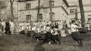 students playing tug of war in 1923, crowd looking on