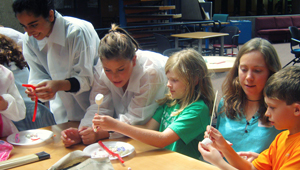 Three Wellesley students work with youngsters to make models of neurons