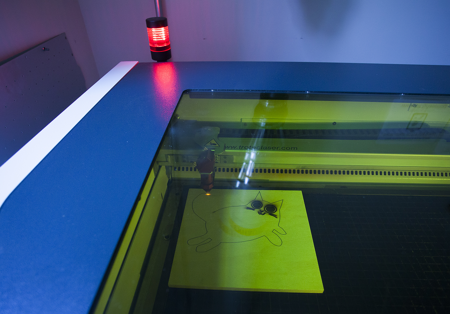 laser cutter machine cutting out a running cat shape on a square piece of wood