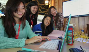 Four students around a computer