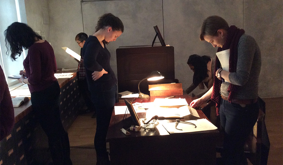 Students look at paper records spread across a table.