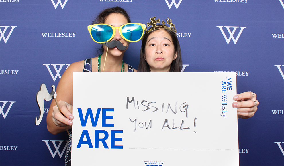 "Alumnae hold a sign during the reunion photo both reading ""We Are Missing You All"""