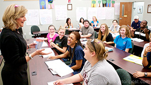 High school students engage with a teacher in a classroom.