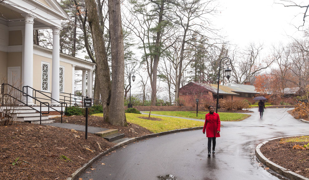 Student walks between Acorns building and Harambee House