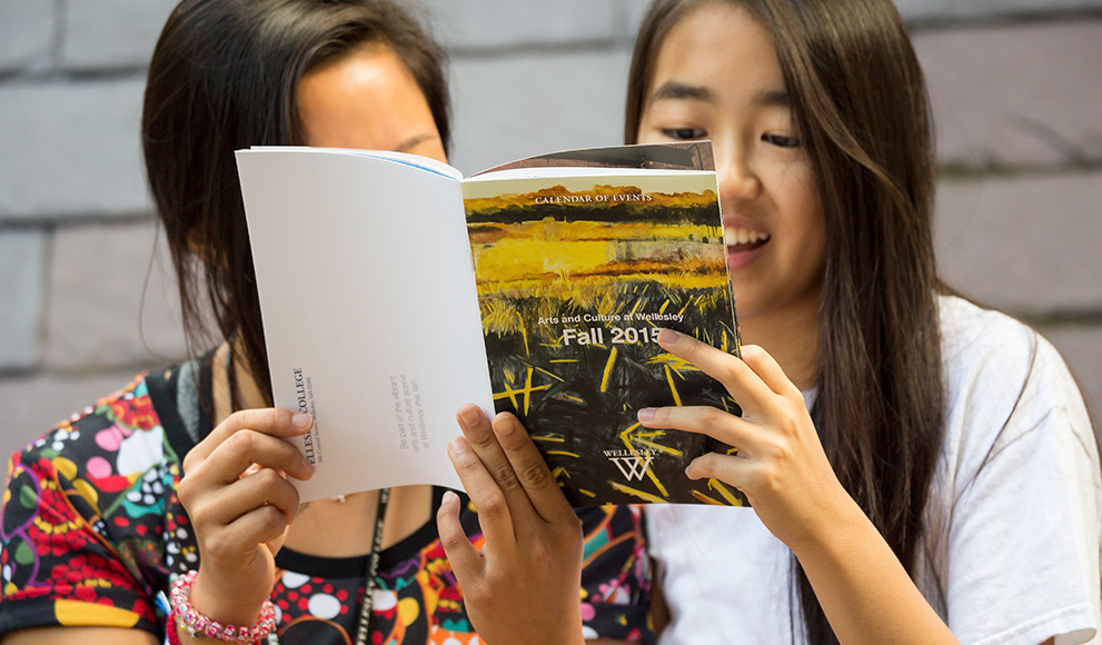 Students read the Fall 2015 Arts Calendar