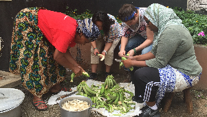 women peeling fruit in Tanzania