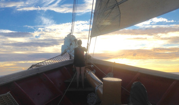 Anthea Fisher '17 watches the sun set over the Mediterranean Sea from the bow of the SSV Corwith Cramer.