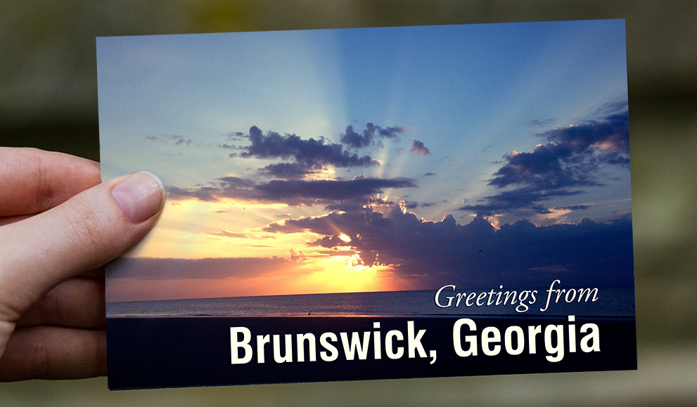 """Hand holds a postcard that reads """"Greetings from Brunswick, Georgia"""""""