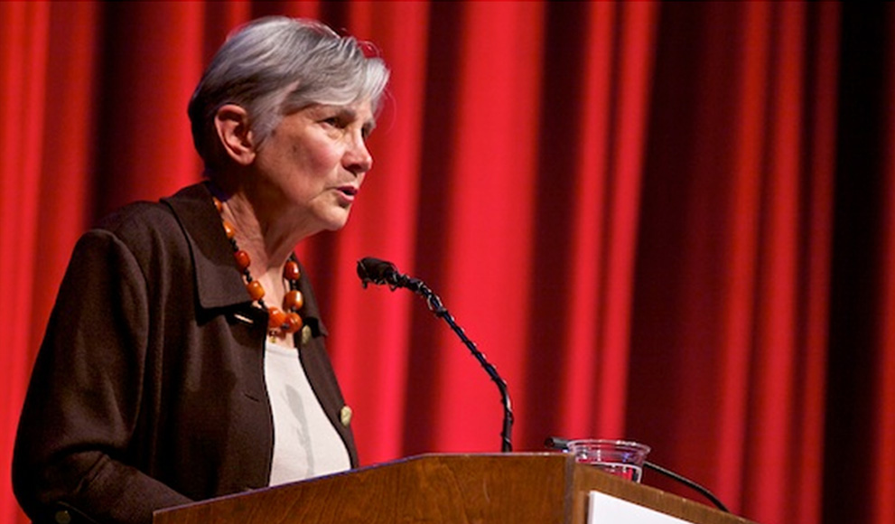 Diane Ravitch '60 speaking on stage in front of a red curtain