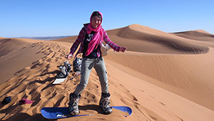 Kathy Long on sandboard in desert