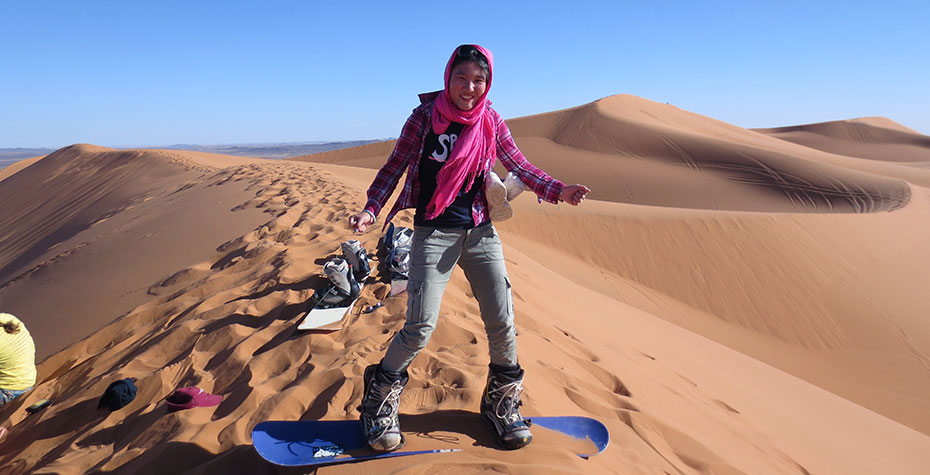 "Kathy Long on a ""sandboard"" about to slide down a desert dune"