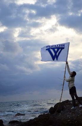 raising a Wellesley flag along a windy shore
