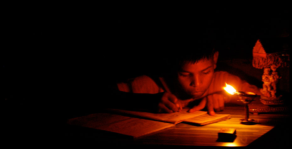young student studies by candlelight in dark