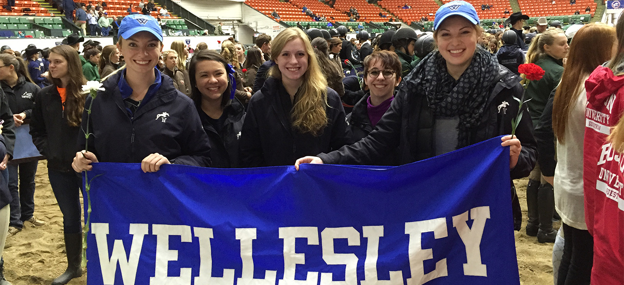 Equestrian team members hold a blue and white Wellesley Banner