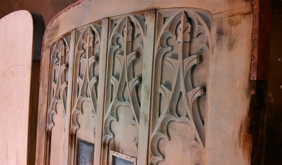 A close-up of an old ornate door stripped of paint