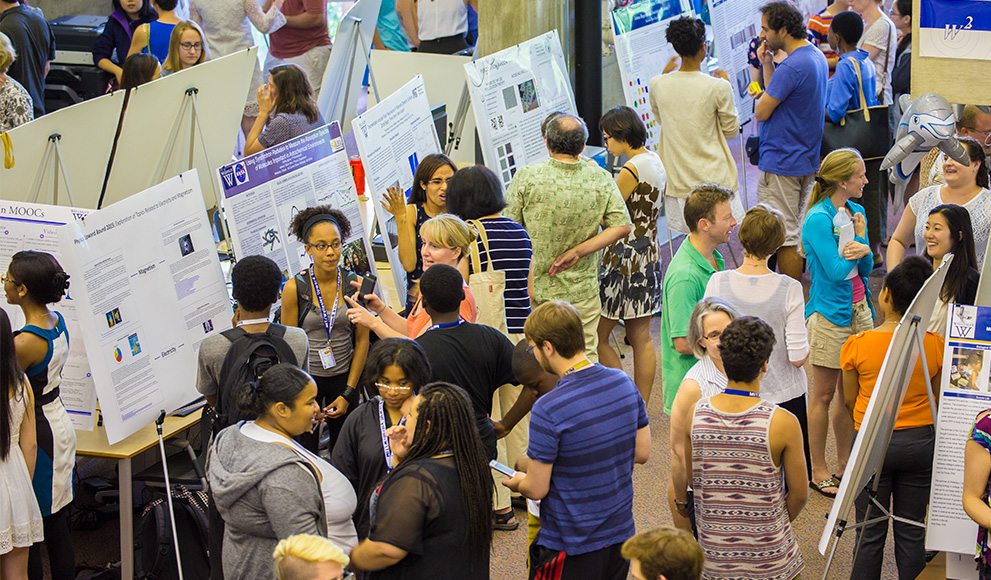 Students, faculty, and visitors gather around posters presenting student summer research.