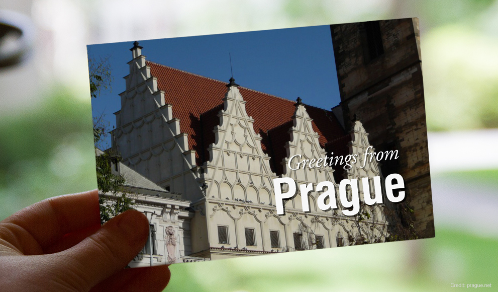 "Hand holds a postcard that reads ""Greetings from Prague"""