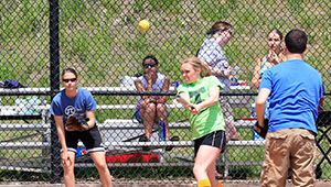 Fans look on from the stands as a softball player hits the ball