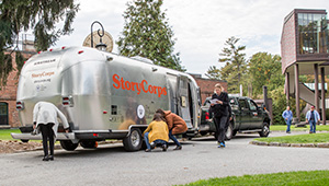 A silver airstream trailer, the StoryCorps MobileBooth, parked near the Wellelsey student center