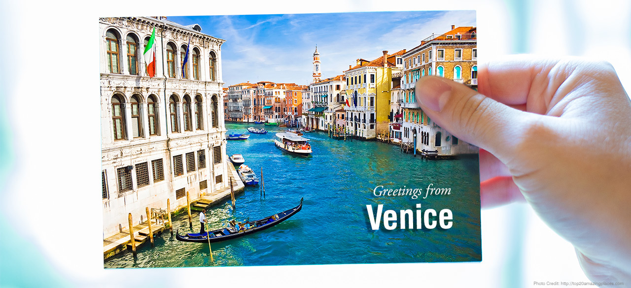 "Hand holds a postcard that reads ""greetings from Venice"""