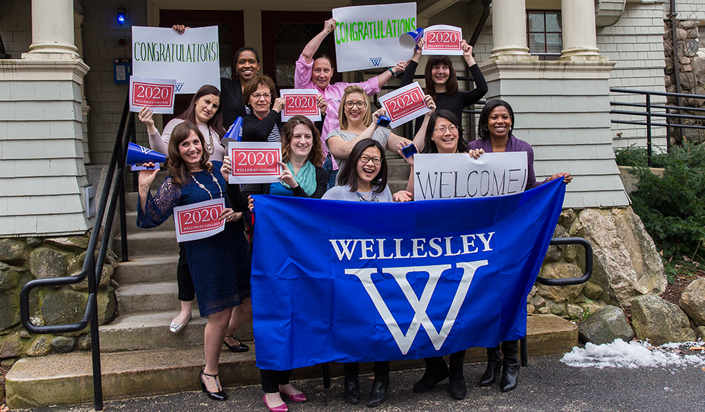 The Admission Office team holds signs welcoming newly-admitted students.