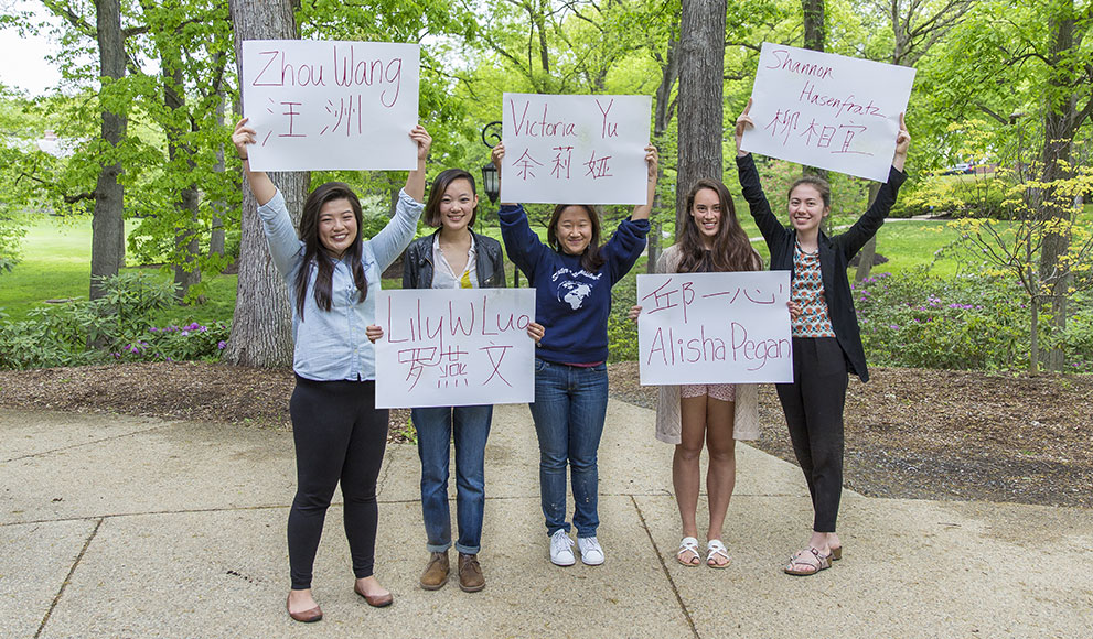 Students hold signs with their names written in English and an alternative alphabet.
