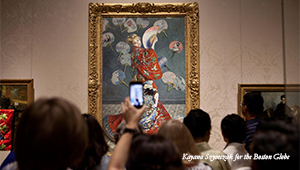 Art patron holds up a cell phone during protest MFA protest in front of Claude Monet painting