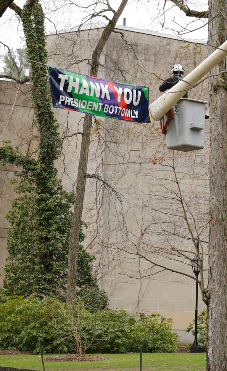 A worker in a bucket truck hangs a sign thanking Wellesley President H. Kim Bottomly.