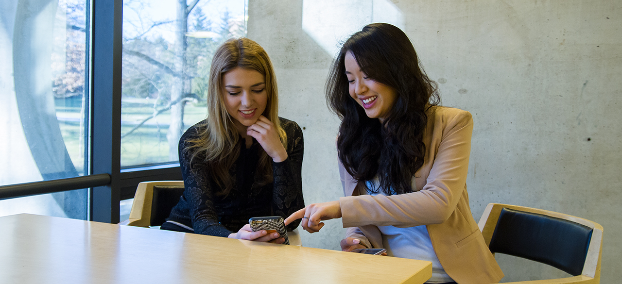 Olivia Joslin '18 and Hannah Wei '18, creators of CliqBit, look at a mobile device