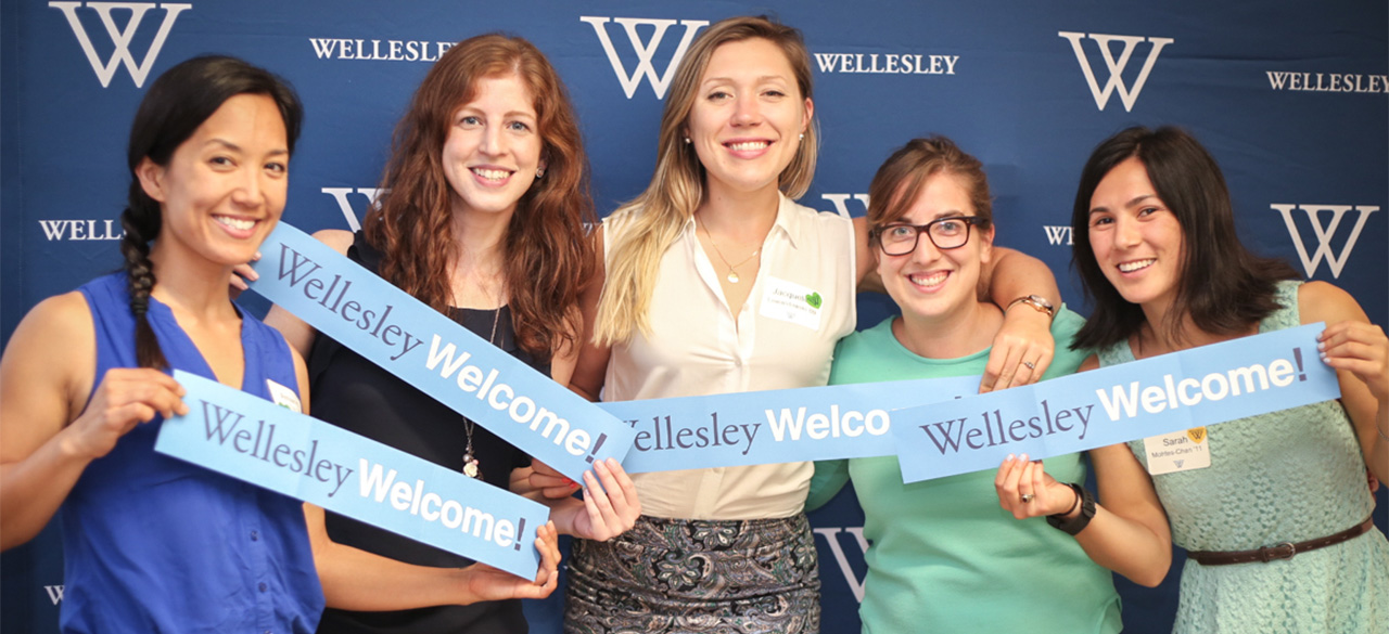 """Alumnae hold """"Wellesley Welcome"""" signs in front of a blue backdrop"""