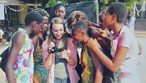 students gather round Hanna Tenerowicz showing images on her camera