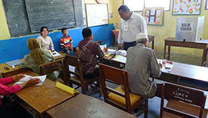 poll workers inside Indonesian schoolroom/polling place