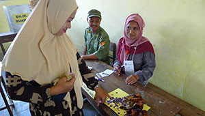 woman in headscarf dips finger in ink at a table in Indonesian voting place