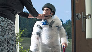 mother strapping helmet on bubble-wrapped kid as he goes out the door