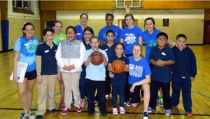 Basketball volunteers pose with students at Let's Get Movin' basketball court