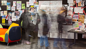 blurred by motion, students gather round bulletin board of hand-written opinions