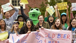 wellesley women and frog mascot wave signs for marathon