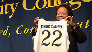 Joanne Berger-Sweeney smiles and holds up Trinity athletic jersey with her last name and number 22 on it