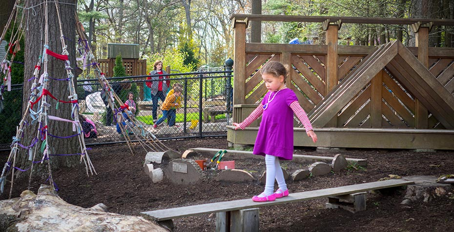 4 year-old girl in purple dress walks a balance beam at Child Study Center playground