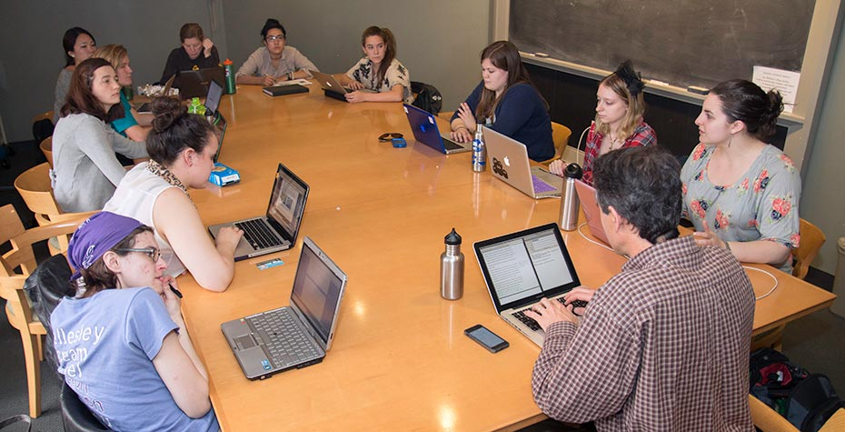 11 students and Jay Turner work around conference table
