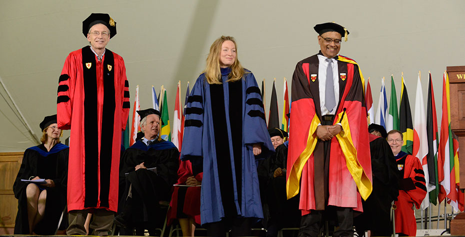 Joe Joyce, Kate Brogan, Chris Arumainayagam on stage in academic robes