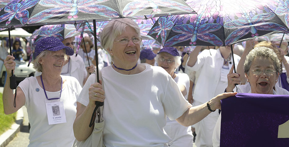 smiling silver-haired alums from a purple class march in parade