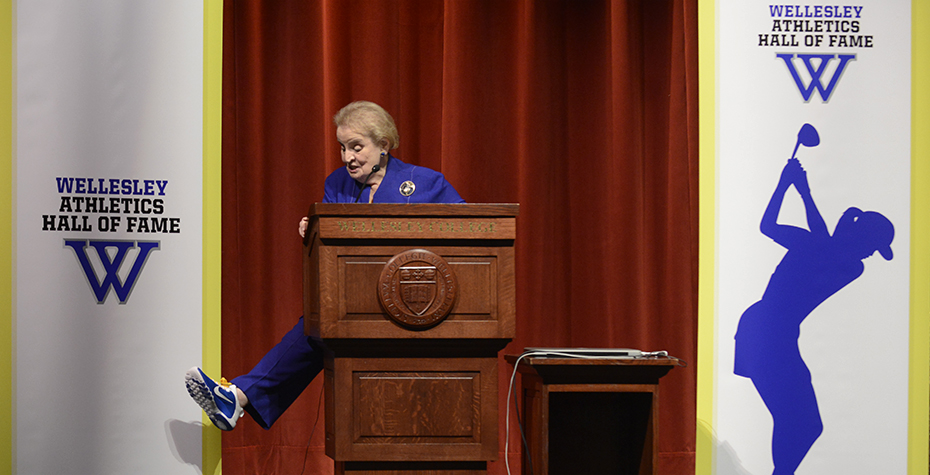 Madeleine Albright shows off blue sneaker from behind podium