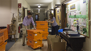 John OKeefe and Lori Tenser move orange rent-a-crates in Green Hall