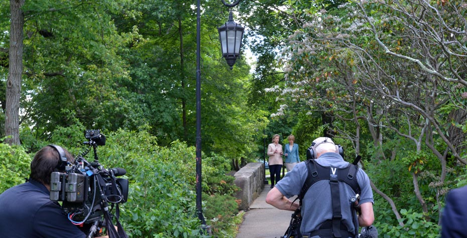 Jane Pauley and Hillary Clinton stJane Pauley and Hillary Clinton stroll on footbridge near Lake Waban as crew filmsroll on footbridge near Lake Waban as crew films
