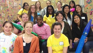 15 diverse Wellesley women pose at Cradles to Crayons