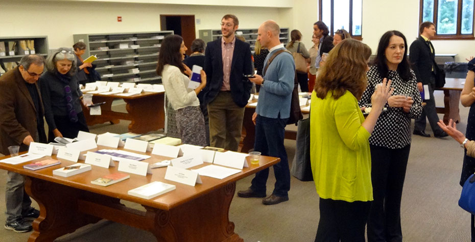 faculty talk, laugh, and look at printed pages together in Clapp reading room